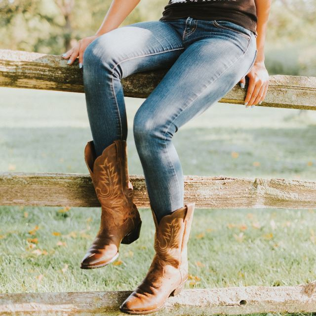 Girl on fence with boots and western wear