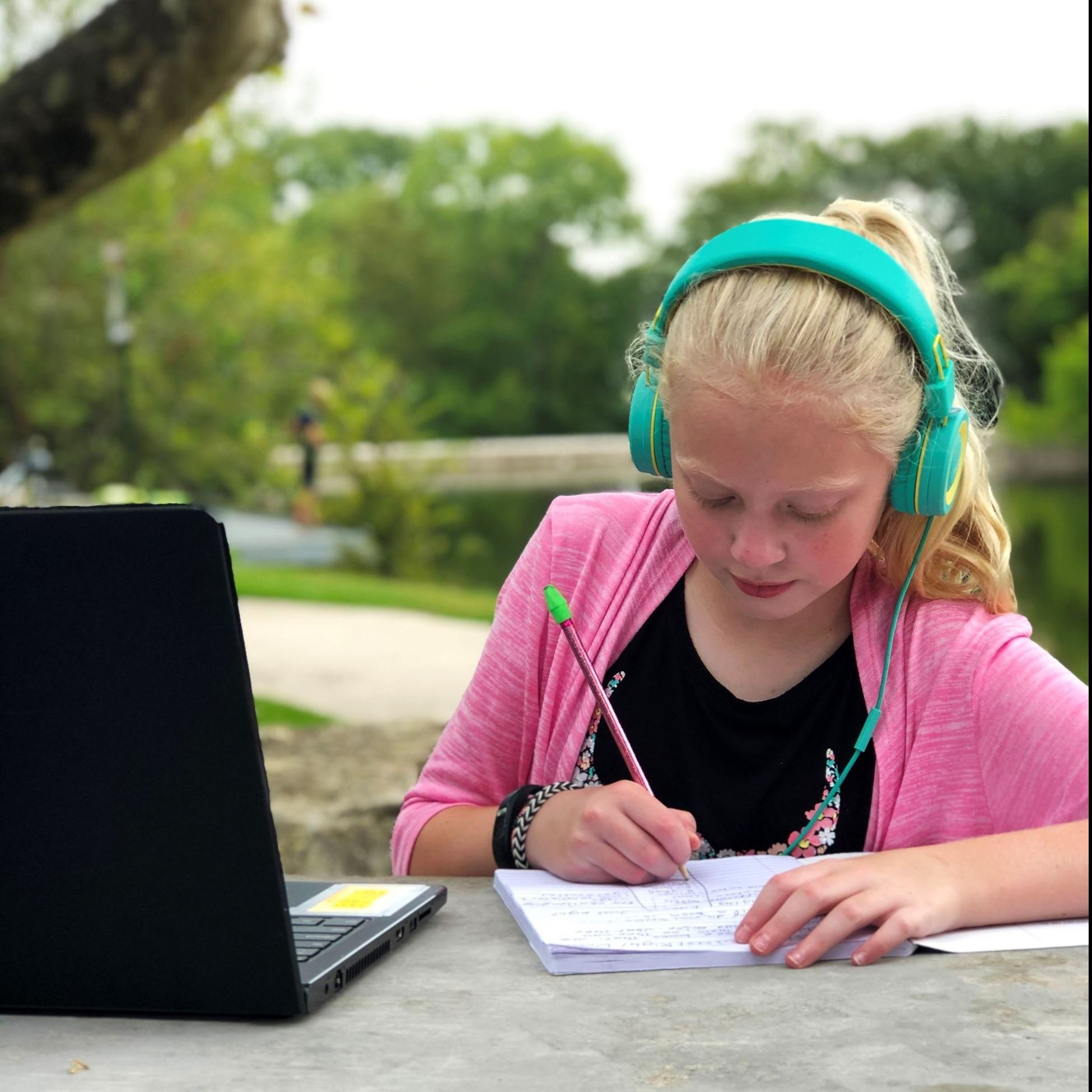 Young girl doing school work outdoors