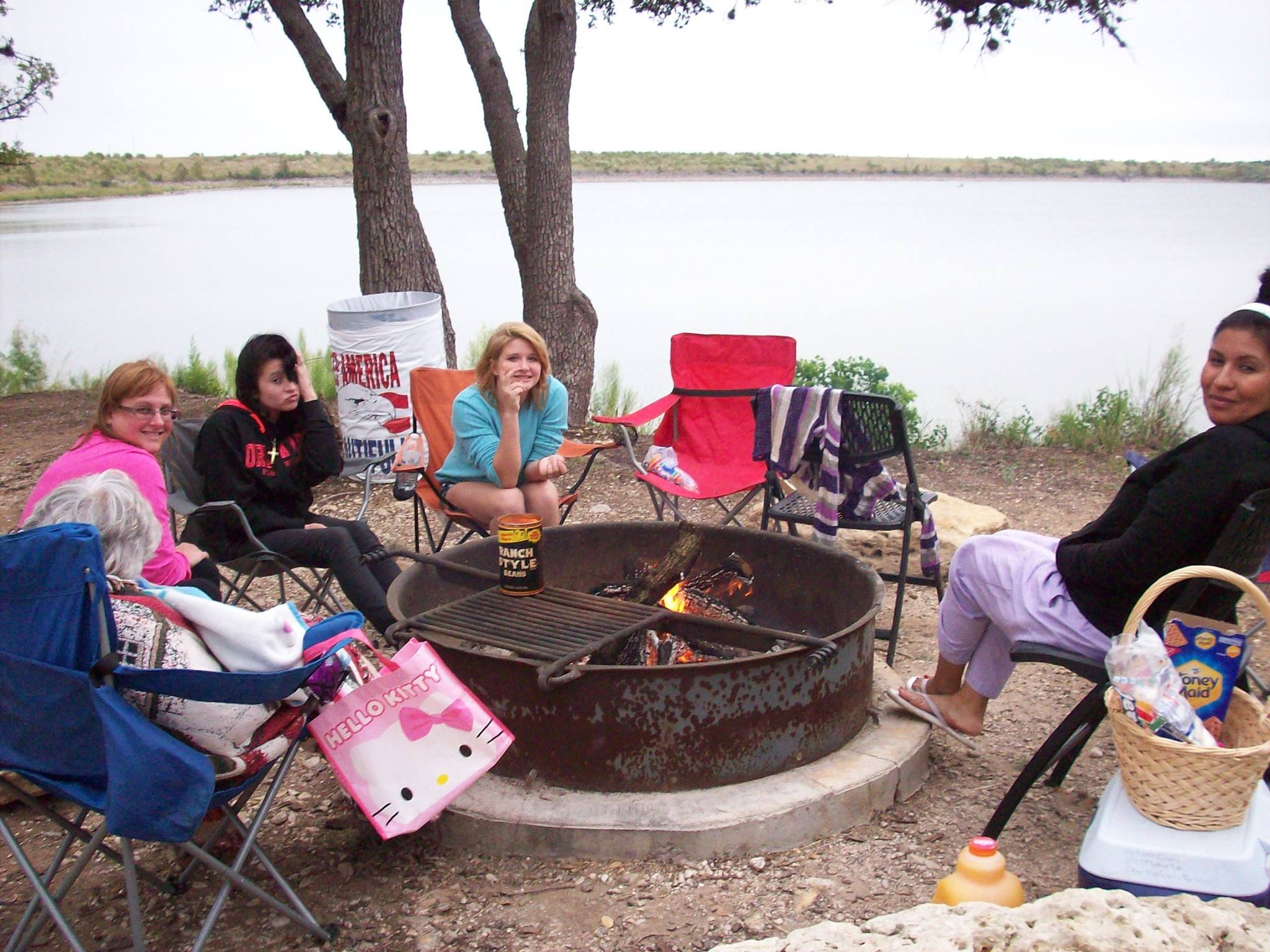Group of 3 Girls Sitting Around a Camp Fire at a Lake